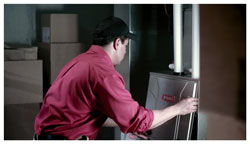 Technician repairing furnace for homeowners