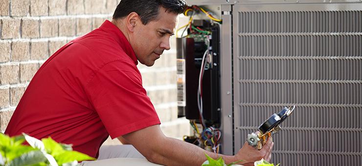 HVAC technician doing routine air conditioner maintenance